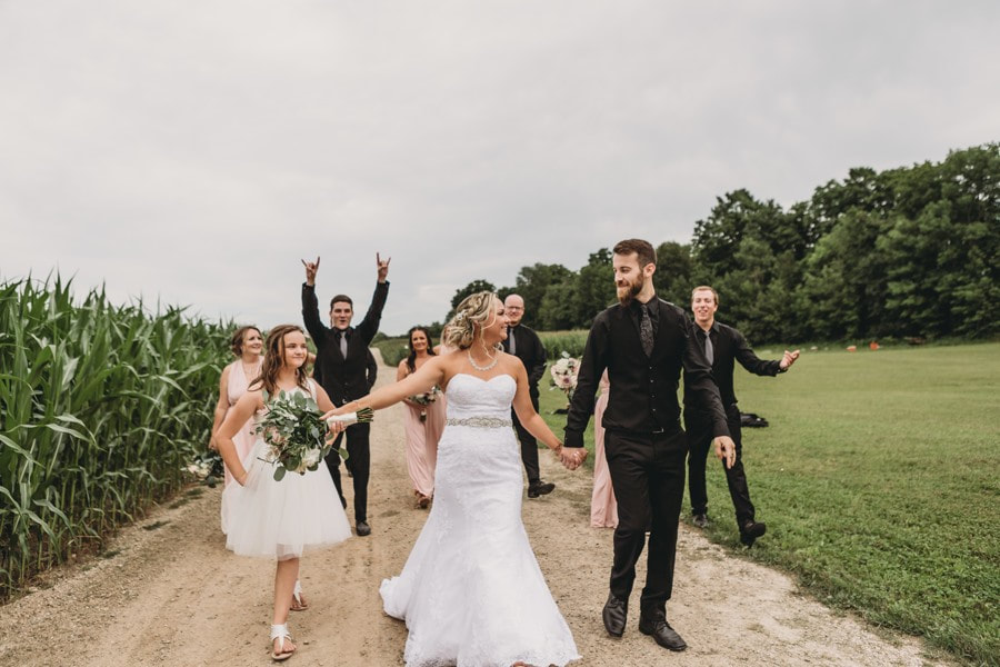Wedding Galleries - Photo of bridal party behind bride and groom, walking down the road in the corn field at Love's Sweet Maple Syrup in Holstien,Ont