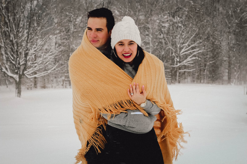 Couple hugging covered in blanket during the winter at Lakeside Park,Kichener,Ontario